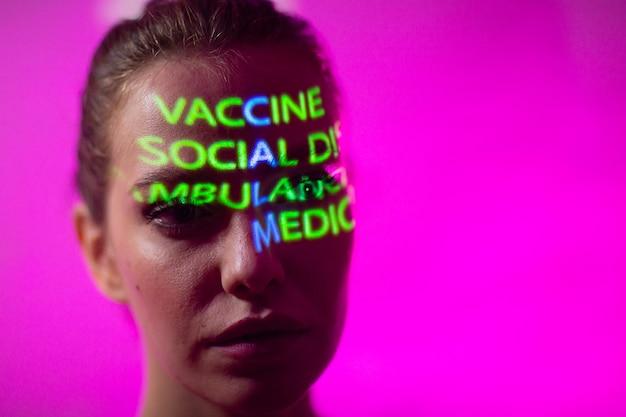 Jonge volwassen vrouw met het woord kalm samengesteld uit woorden vaccin sociale afstand ambulance en medische verzekering op haar gezicht