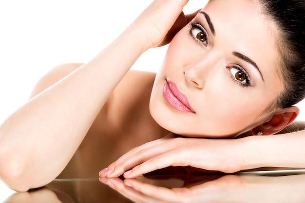 Jonge volwassen vrouw met mooi die gezicht - op wit wordt geïsoleerd. huid zorg concept.