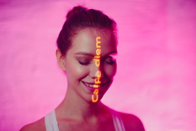 Jonge volwassen vrouw met spreekwoordelijke woorden carpe diem vertaald uit het latijn als pluk de dag op haar gezicht