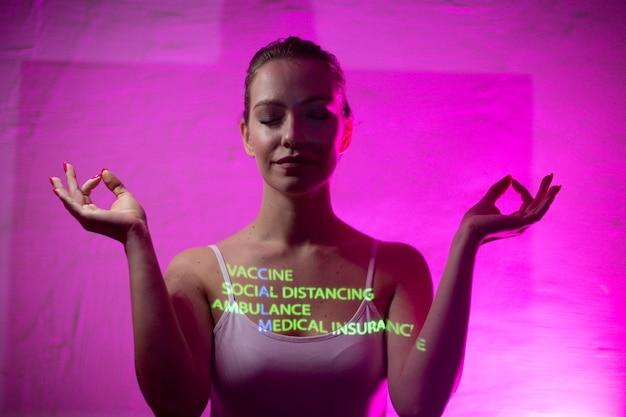 Jonge volwassen vrouw met woord calm samengesteld uit woorden vaccin social distance ambulance en medische verzekering op haar lichaam.