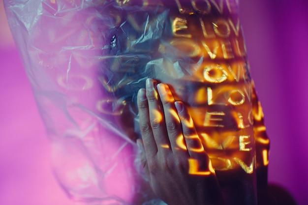 Jonge volwassen vrouw met woord love op haar hoofd in plastic zak