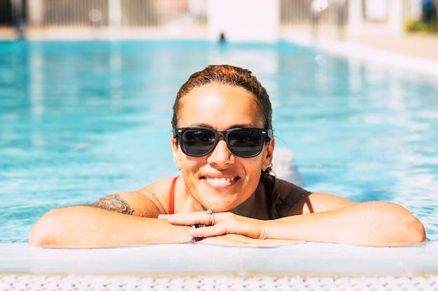 Jonge volwassen vrouw portret glimlach uit het water bij het zwembad genieten van actieve en vakantie levensstijl