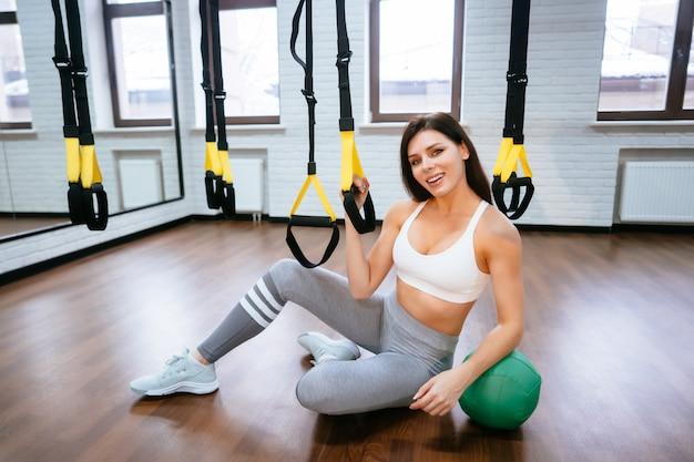 Jonge volwassen vrouw poseren in de sportschool