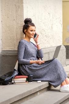 Jonge volwassen vrouwelijke student praten door smartphone zittend op trappen met laptop in de buurt van universiteitsgebouw