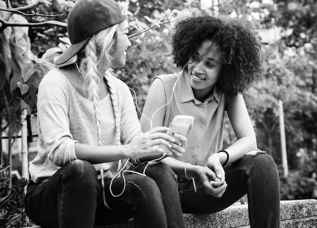 Jonge volwassen vrouwelijke vrienden luisteren naar muziek via hun smartphone buitenshuis