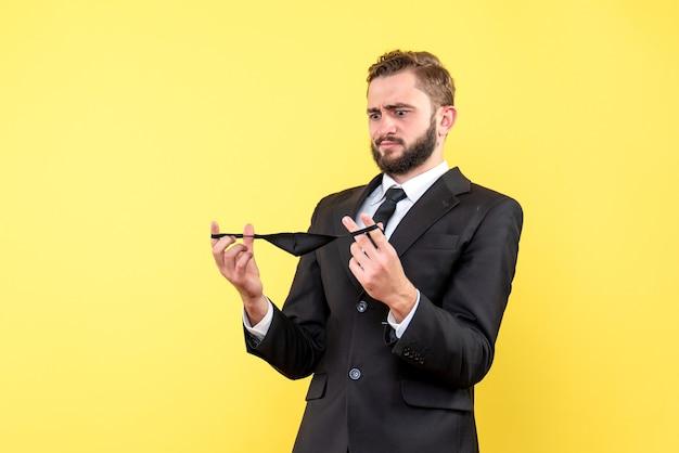 Jonge volwassen zakenman twijfelt over het dragen van een masker op geel