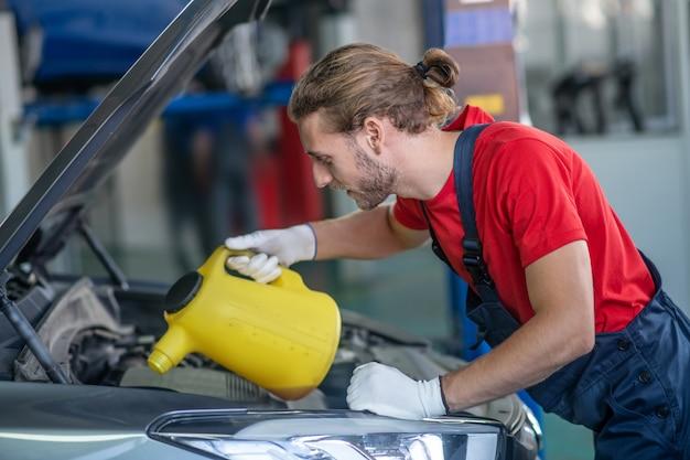 Jonge volwassen zelfverzekerde man in werk uniform bezig met auto's