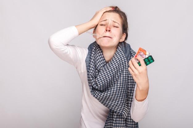 Jonge volwassen zieke vrouw heeft temperatuur en houdt veel pillen vast. studio-opname, geïsoleerd op een grijze achtergrond