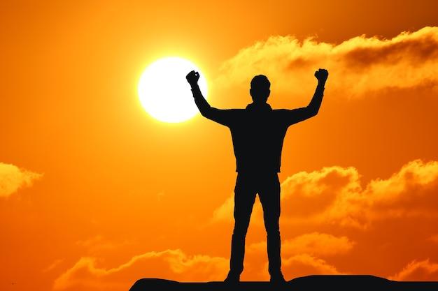 Jonge volwassene die armen naar de zee steekt bij zonsondergang, handen omhoog