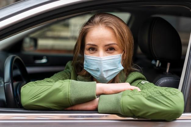 Jonge volwassene die een beschermingsmasker in de auto draagt