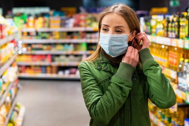 Jonge volwassene die een beschermingsmasker in een winkel draagt