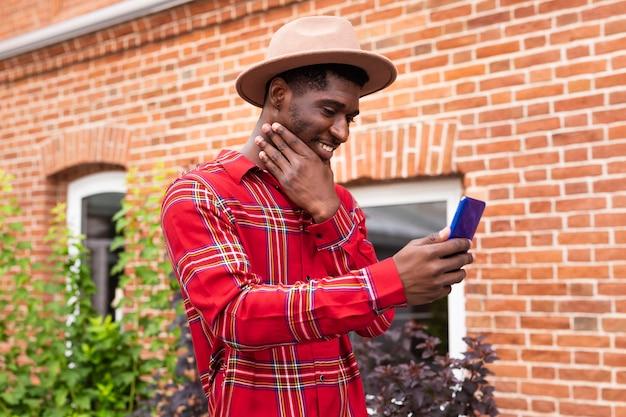 Jonge volwassene die in rood overhemd een close-up selfie neemt