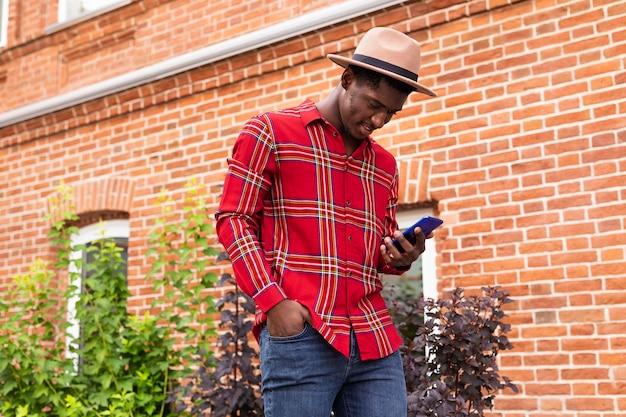 Jonge volwassene die in rood overhemd zijn telefoon bekijkt