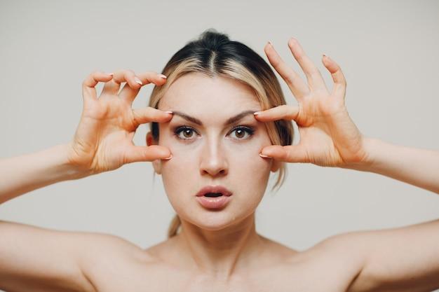 Jonge volwassene die zelfmassage van gezichtsgymnastiek en verjongende oefeningen doet, gezichtsbouw voor het opheffen van huid en spieren