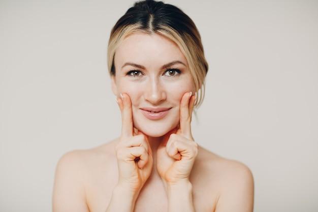 Jonge volwassene die zelfmassage van gezichtsgymnastiek en verjongende oefeningen doet gezichtsbouw voor het opheffen van huid en spieren