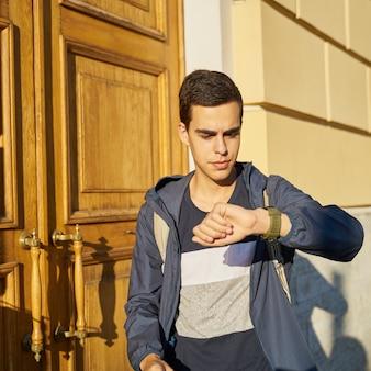 Jonge volwassene kijkt horloge. benadrukt blanke man met zwart haar bang om laat te worden