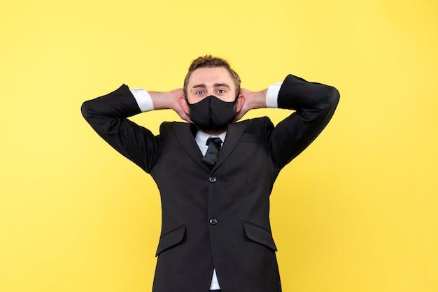 Jonge volwassene met handen achter hoofd op geel