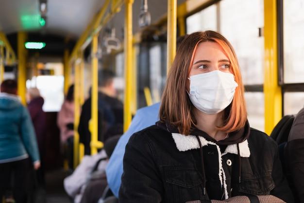 Jonge volwassene pendelt in een beschermend gezichtsmasker. coronavirus, covid-19-concept voor verspreidingpreventie, verantwoordelijk sociaal gedrag van een burger