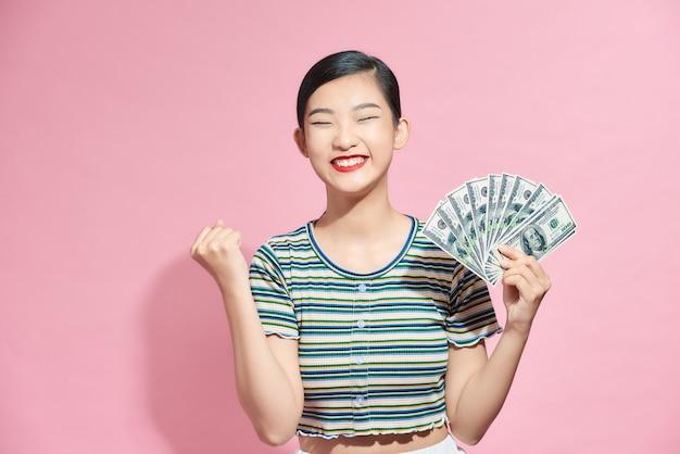 Jonge volwassene vrouw blij en enthousiast met een fan van geld in de studio
