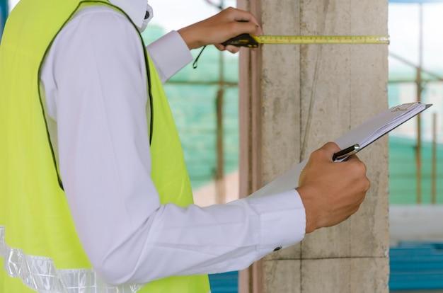 Jonge voorman bouwer ingenieur of inspecteur controleren en inspecteren met klembord en meetlint op bouwplaats bouwen