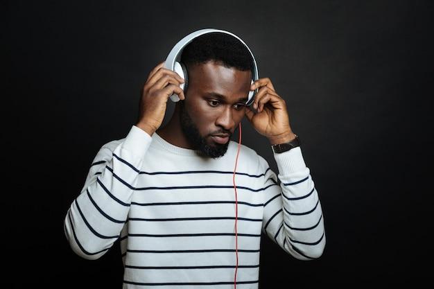 Jonge vreedzame man die een koptelefoon gebruikt en naar de muziek luistert terwijl hij geïsoleerd tegen een zwarte muur staat