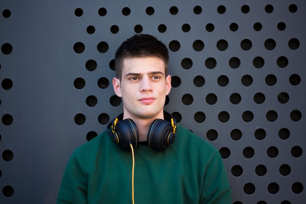 Jonge vreedzame man met een koptelefoon wegkijken
