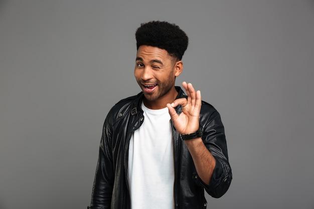 Jonge vriendelijke afrikaanse man knipoogt één oog terwijl ok gebaar wordt getoond