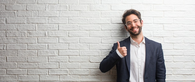 Jonge vriendelijke bedrijfsmens opgewekt en opgewekt, glimlachend en haar duim opheffen