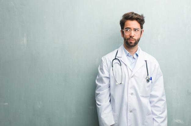 Jonge vriendelijke dokter man tegen een grunge muur met een kopie ruimte twijfelen en verward, denken aan een idee of bezorgd over iets
