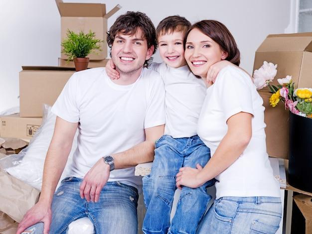 Jonge vriendelijke en gelukkige familie zitten samen in hun nieuwe flat