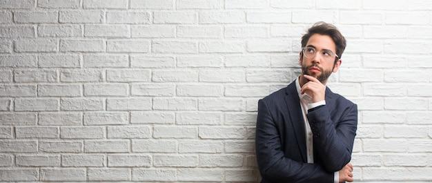 Jonge vriendelijke zakenman denken en opzoeken, verward over een idee