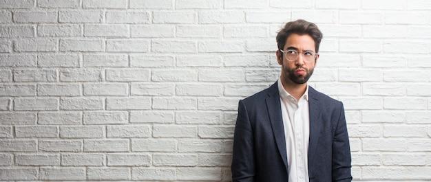 Jonge vriendelijke zakenman twijfelt en verward, denkend aan een idee of bezorgd over iets