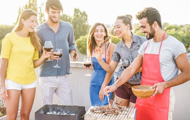 Jonge vrienden die barbecuepartij hebben bij zonsondergang op huisterras