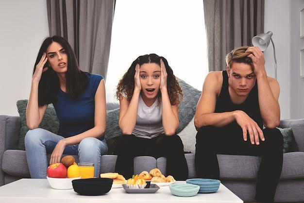 Jonge vrienden die emoties maken terwijl ze samen thuis tv kijken