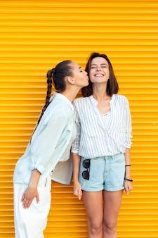 Jonge vrienden die haar vriend op de wang kussen