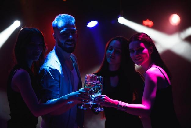 Jonge vrienden die met glazen champagne in handen dansen.