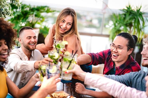 Jonge vrienden die mojito-drankjes roosteren in de cocktailbar op het dak