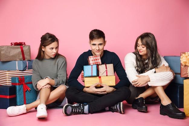 Jonge vrienden die onder de dozen van de kerstmisgift op roze zitten