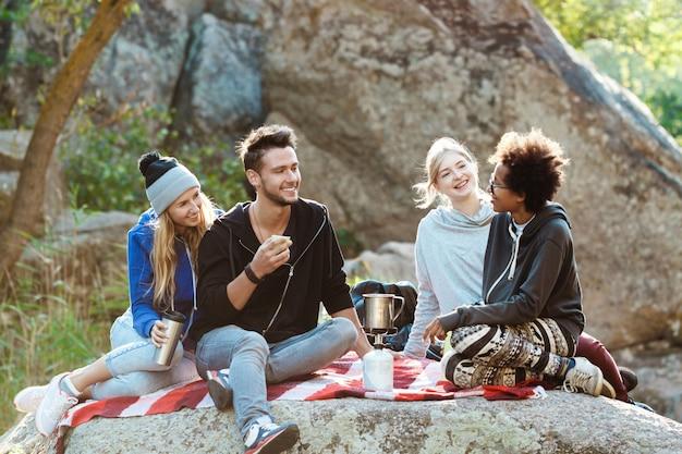 Jonge vrienden die op rots in canion zitten, glimlachen, die thee drinken