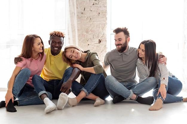 Jonge vrienden die op vloer samen zitten
