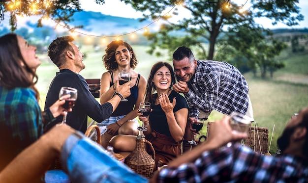 Jonge vrienden die plezier hebben in de wijngaard na zonsondergang