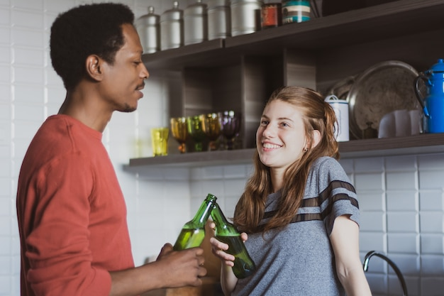 Jonge vrienden die pret met flessen hebben thuis.
