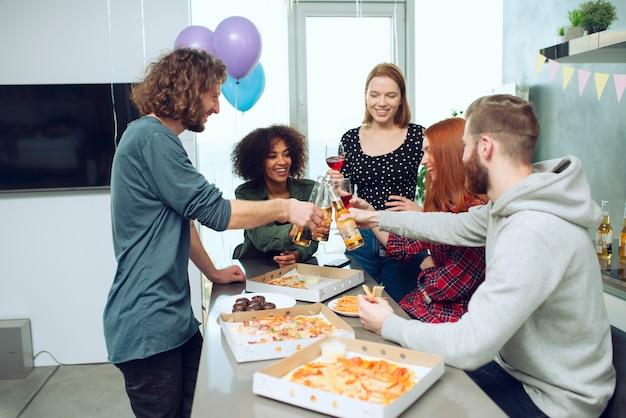 Jonge vrienden eten pizza en drinken bier met plezier samen thuis feestje