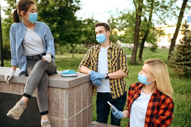 Jonge vrienden in maskers en handschoenen vrije tijd in park, quarantaine. vrouwelijke persoon wandelen tijdens de epidemie, gezondheidszorg en bescherming, pandemische levensstijl