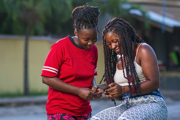 Jonge vrienden kijken naar de smartphone op straat Gratis Foto