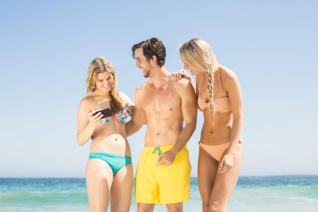Jonge vrienden kijken naar mobiele telefoon op het strand