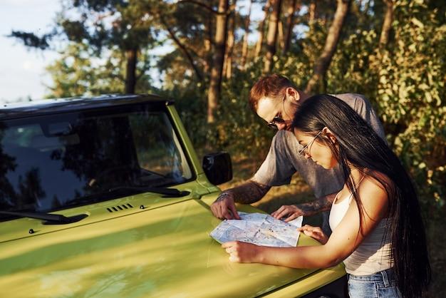 Jonge vrienden lezen kaart die op de motorkap van moderne groene jeep in het bos staat.