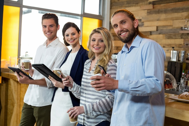 Jonge vrienden met behulp van digitale tablet en mobiele telefoon terwijl het hebben van koffie