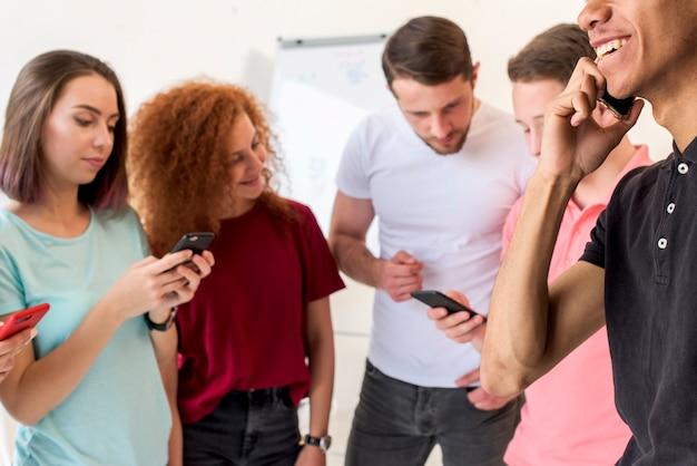 Jonge vrienden met behulp van slimme telefoons voor communicatie