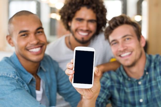 Jonge vrienden met zwart scherm van smartphone op camera